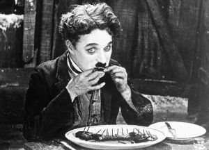 "Charlie Chaplin eats his boot in ""The Gold Rush."""